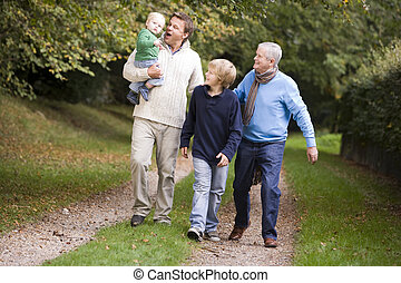 Garndfather Father and grandsons walking on path outdoors