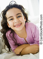 Young girl in living room smiling high key