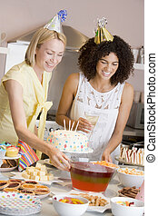 Two women at party setting out food smiling