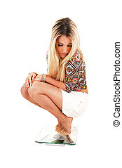 Girl crouching on scale - A young slim woman crouching bare...