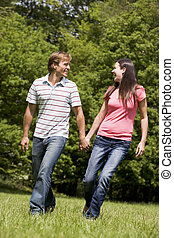 Couple walking outdoors holding hands smiling