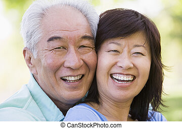 Couple relaxing outdoors in park laughing