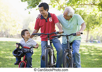 Grandfather son and grandson bike riding