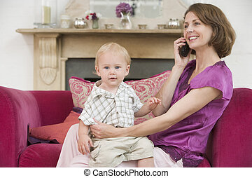 Mother using telephone in living room with baby smiling