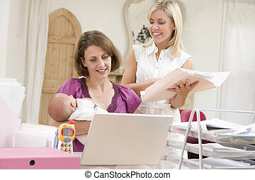 Two women and a baby in home office with laptop