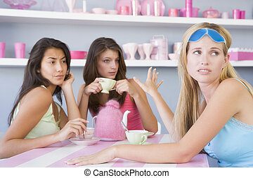 Young woman with a hangover sitting at a table with two...