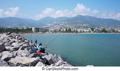 Fishers sitting on rocks in Alanya, Turkey - ALANYA, TURKEY...