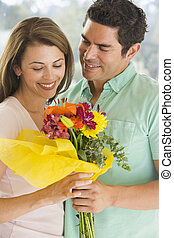 Husband giving wife flowers and smiling