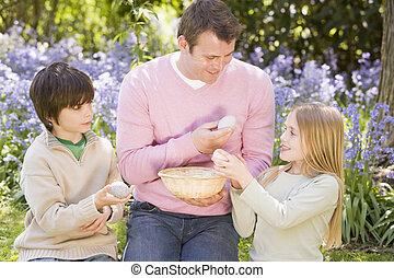 Father and two young children on Easter looking for eggs outdoors smiling