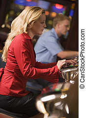 Woman in casino playing slot machine with people in background (selective focus)