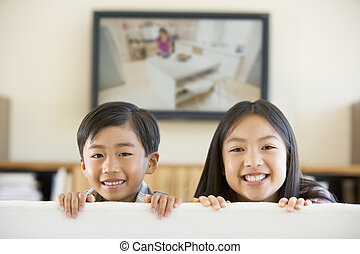 Two young children in living room with flat screen...