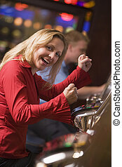 Woman in casino excited playing slot machine with people in background (selective focus)