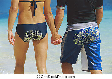 Couple holding hands at the beach (selective focus)