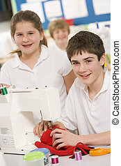 Male and female student using sewing machine
