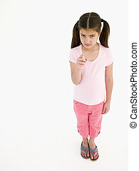 Young girl pointing and frowning
