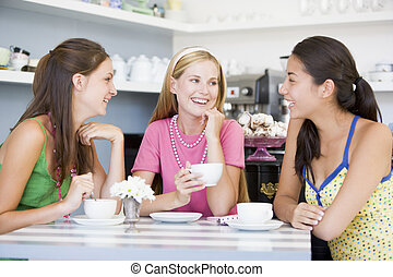 Three young woman sitting at a table and drinking tea