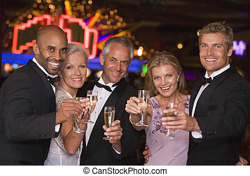 Five people in casino with champagne smiling selective focus...