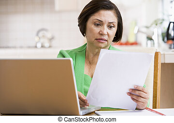 Woman in kitchen with laptop and paperwork looking worried