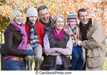 Family outdoors in park smiling (selective focus)