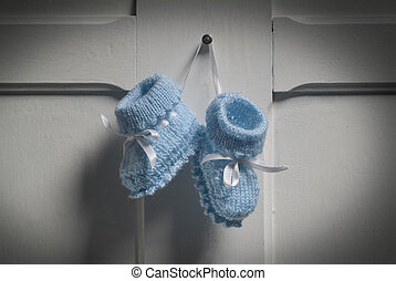 Baby Booties - Blue Baby Booties hanging on white door