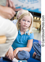 Student in class sitting on floor looking at teacher (selective focus)