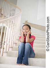 Young Girl Sitting On A Stairwell At Home