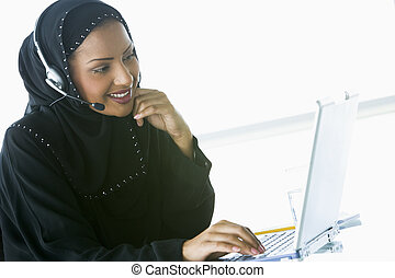 Woman wearing headset with laptop smiling (high...
