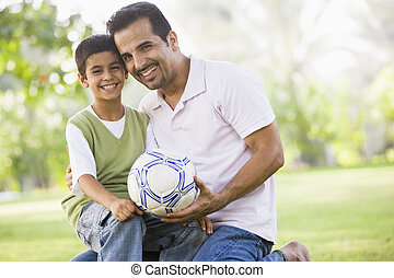 Father and son outdoors in park with ball smiling (selective...
