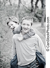 Cute brothers laughing giving piggyback ride - Cute...
