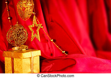 Golden christmas decoration and gift on red fabric...