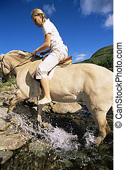 Woman outdoors riding horse through stream (fisheye)