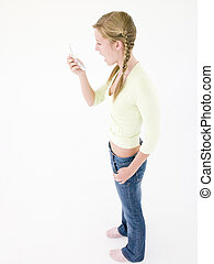 Teenage girl looking at cellular phone in shock