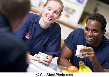 Three firefighters in break room drinking coffee and talking...