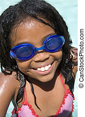 Young girl in swimming pool wearing goggles smiling