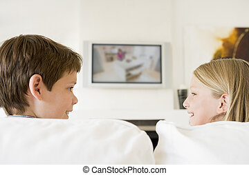 Young boy and young girl in living room with flat screen television