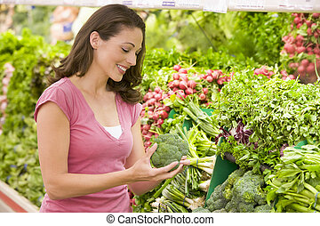 Woman shopping for broccoli at a grocery store