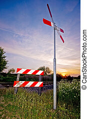Railroad sign with sunset - crossing railroad sign with a...
