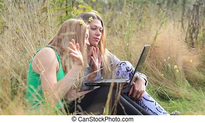 Female friends with laptop outdoor.