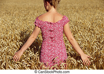 Woman standing outdoors in wheat field selective focus