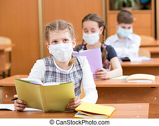 school kids with protection mask against flu virus at lesson