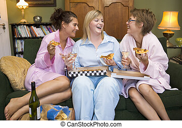 Three woman in night clothes sitting at home eating pizza