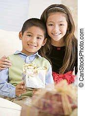 Brother And Sister Sitting On Couch Holding Christmas Gift