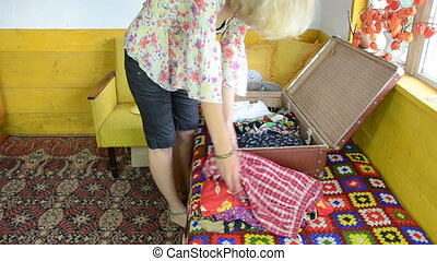 girl unpack suitcase - Girl on colorful room sofa unpacking...