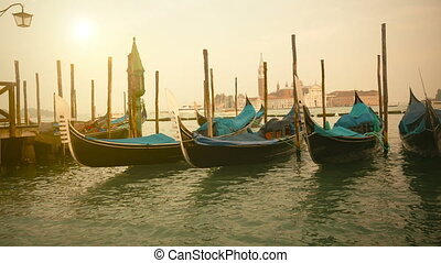 Venetian gondolas at sunrise tied near the pier on San Marco...