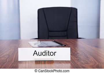 Nameplate With Auditor Title Kept On Desk In Front Of Empty...