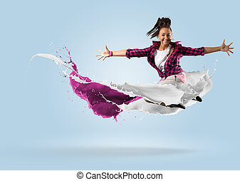 young female dancer jumping with splash of paint - young...
