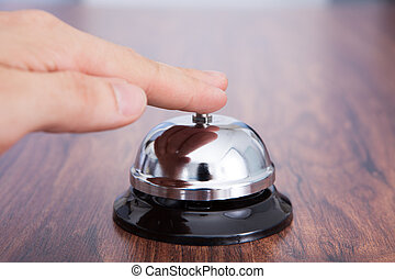 Hand Ringing Service Bell Kept On Wooden Table - Close-up Of...