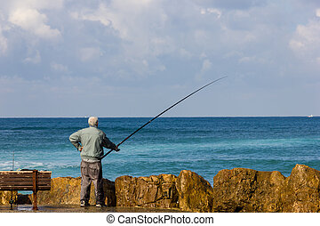 fisherman with a fishing rod on sea