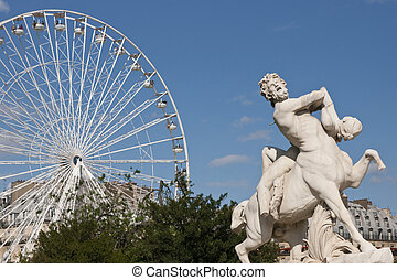 Jardin des Tuileries - Statue and white ferris wheel in the...