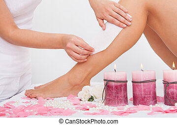 Beautician Waxing A Woman's Leg Applying Wax Strip